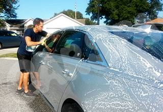 Car washes vs mobile detailing. Owner of car Spa Orlando washing a silver Cadillac CTS