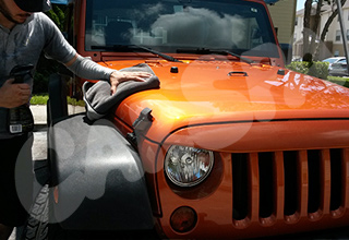 Mobile detailing services car wax application on vehicle