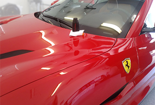 Picture of a ferrari portofino with a nl272 ceramic coating bottle on top of the hood protected with small microfiber towel.